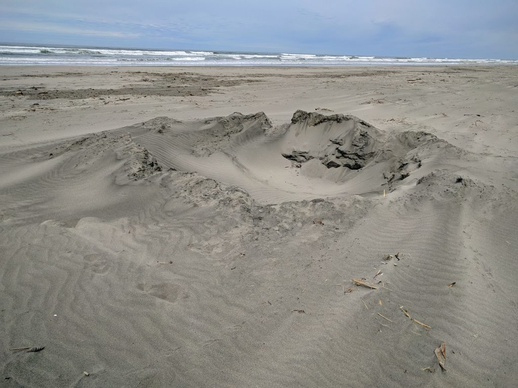 Sandy beach with interesting hole in it.